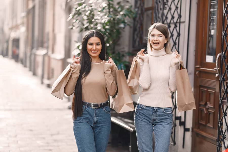 happy young women with shopping bags walking on street
