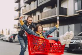 man riding girl on shopping trolley on parking