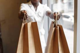 crop seller passing purchases in paper shopping bags