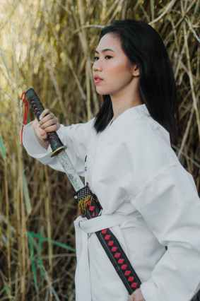 woman in white long sleeve clothing holding a sword